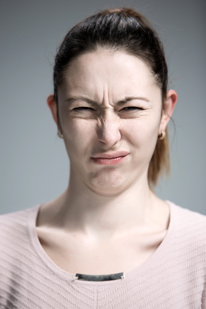 emotion faces: The portrait of disgusted woman on gray