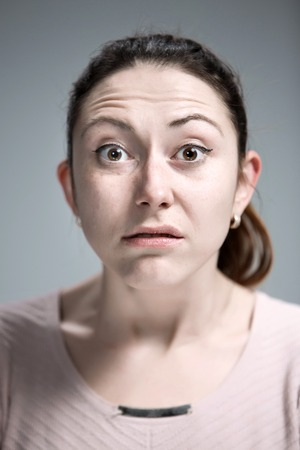 disgusted: The portrait of disgusted woman on gray