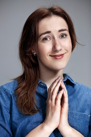 Woman wearing a blue shirt is looking imploring. Over gray background