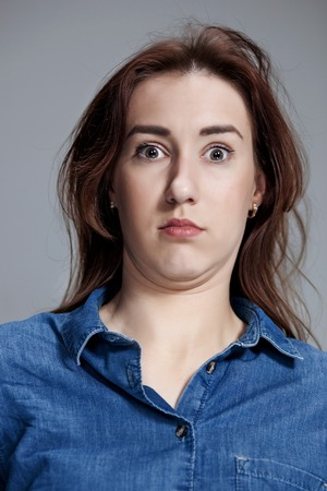 wonderment: Portrait of young woman with shocked and surprised facial expressions over gray background Stock Photo