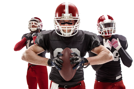 three persons: The three caucasian fitness men as american football players posing with a ball on white background
