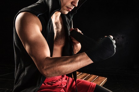 The hands with bandage of muscular man training kickboxing on black