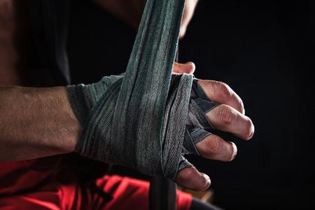 Close-up hand met een bandage van gespierde man opleiding kickboxing op zwart Stockfoto