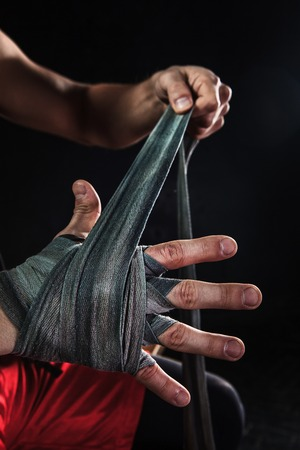 Close-up hands with bandage of muscular man training kickboxing on black