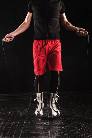 skipping rope: The legs of muscular man with skipping rope training kickboxing  on black