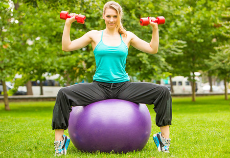Young beautiful sports girl sitting on fitball with dumbbells in the park on a background of green grass Stock Photo
