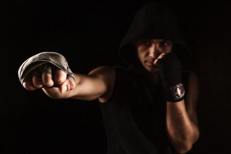 Primer plano de mano con el vendaje de las funciones muscular kickboxing entrenamiento del hombre en negro Foto de archivo - 54261276