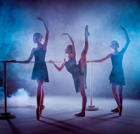 flexable: The silhouettes of young ballerinas stretching on the bar on blue smoke background