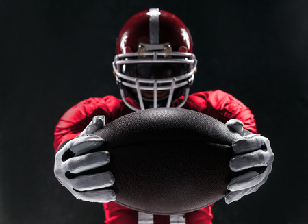 Caucasian fitness man as american football player holding a ball on black background Stock Photo