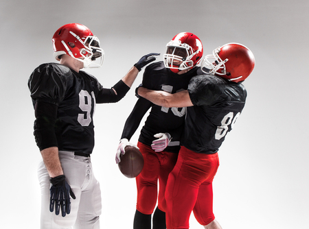 rejoicing: The three caucasian fitness men as american football players posing  as winners on white background and rejoicing