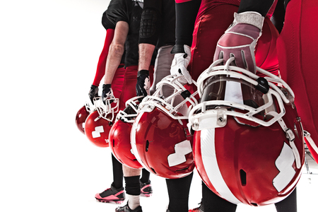 The hands of five american football players with helmets on white background