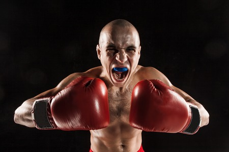 kickboxing: The young male athlete kickboxing on a black background  with kapa in mouth. concept fury in the fight Stock Photo