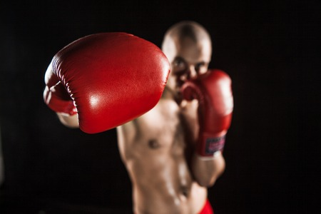 thai people: The young male athlete kickboxing on a black background Stock Photo