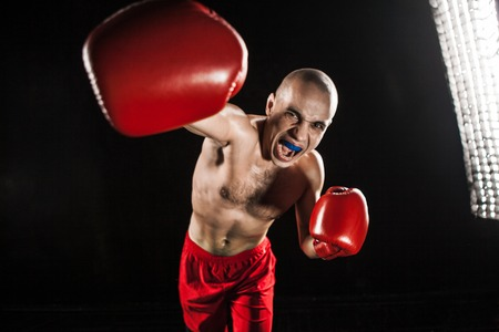 fury: The young male athlete kickboxing on a black background  with kapa in mouth. concept fury in the fight Stock Photo