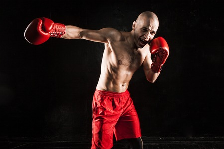 kickboxing: The young male athlete kickboxing on a black background Stock Photo
