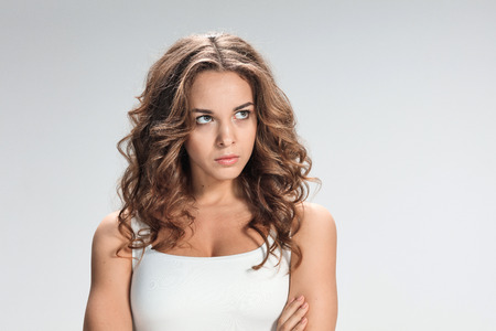 disgusted: The portrait of disgusted and disaffected woman on gray Stock Photo