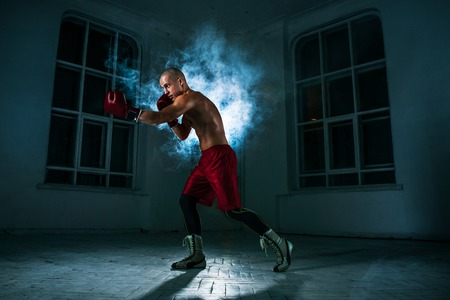 kickboxing: The young male athlete kickboxing on a background of blue smoke