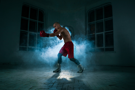 muscle boy: The young male athlete kickboxing on a background of blue smoke