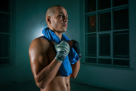 kickboxing: The young male athlete kickboxing on a black background with a towel after a workout