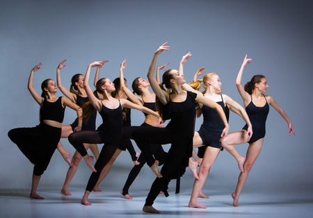 The group of modern ballet dancers dancing on gray background