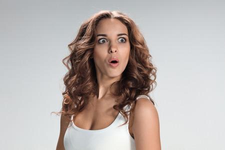 Retrato de mujer joven con la expresión facial sorprendida sobre fondo gris