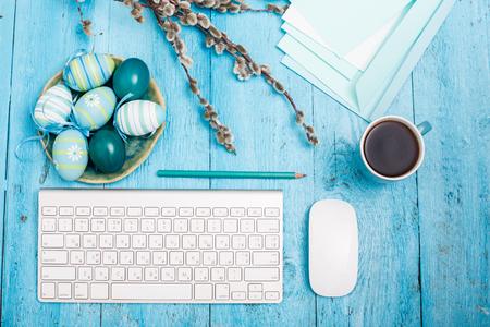 青い木製のテーブルで仕事場でイースター。コンピューターのキーボードと一杯のコーヒー 写真素材