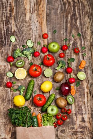 tiendas de comida: Las verduras y frutas frescas de una bolsa de papel sobre una mesa de madera