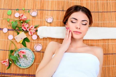 Schöne junge Frau an einem Badekurortsalon, der auf einer Strohmatte stillsteht. Konzept der Körperpflege und Entspannung