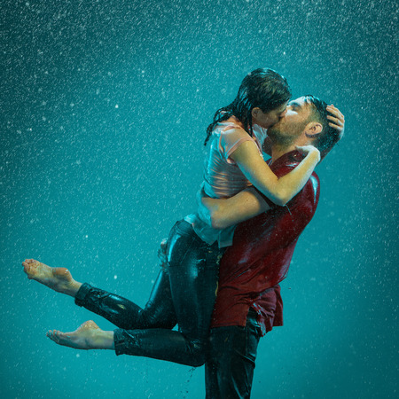 The loving couple kissing in the rain on a turquoise background Stok Fotoğraf