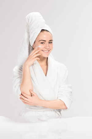 bath gown: The cute nice girl with cream in her face on gray background