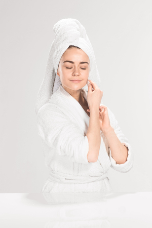 removing make up: Woman cleaning face in  bathroom on gray background