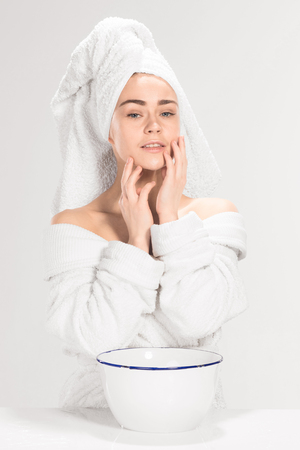 woman washing face: The young woman washing face with clean water Stock Photo