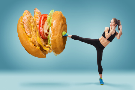 Fit, young, energetic woman boxing unhealthy food on blue background. Concept of diet and healthy lifestile