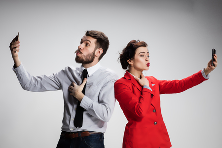 companion: Business concept. The two young colleagues holding mobile phones on gray background  and kissing his companion Stock Photo