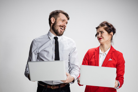 offend: The young businessman and businesswoman with laptops communicating on gray background. The concept of relationship of colleagues Stock Photo