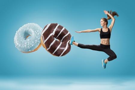 Ajuste a la mujer joven que lucha contra la mala comida sobre un fondo azul. El concepto de dieta sana y lifestile Foto de archivo