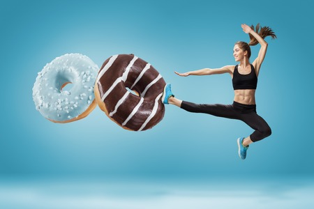 Fit młoda kobieta odpierając złe jedzenie na niebieskim tle. Koncepcja diety i zdrowego lifestile