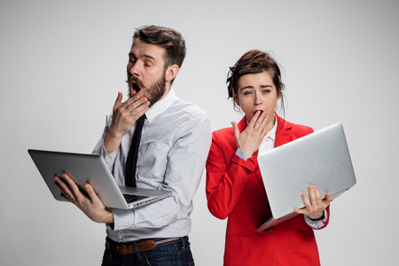 mockery: The  yawning and bored young businessman and businesswoman with laptops on gray background. The concept of relationship of colleagues. Stock Photo