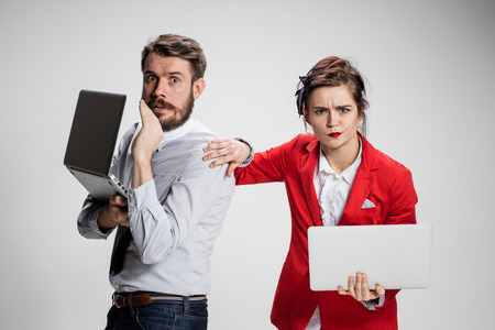 mockery: The young businessman and businesswoman with laptops communicating on gray background. The concept of relationship of colleagues Stock Photo