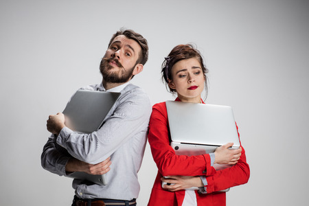 The young businessman and businesswoman with laptops posing on gray background. The concept of relationship of colleagues and of love in the work Stock Photo