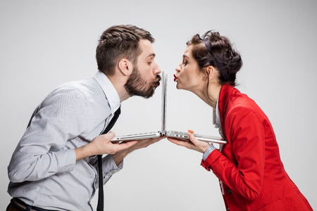 Blind Date: Love on the Internet. The young businessman and businesswoman with laptops kissing screens on gray background Stock Photo