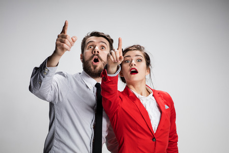 The funny surprised business man and woman showing up on a gray background. Business concept  of relationship Archivio Fotografico