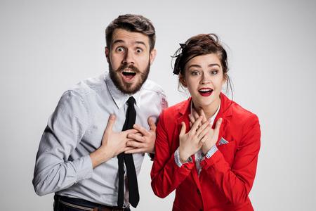 De grappige verraste bedrijfsman en vrouw die op een grijze achtergrond glimlachen. Bedrijfsconcept relatie