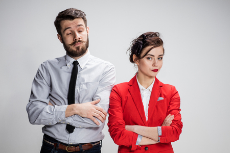 conflicting: The funny sad business man and woman conflicting on a gray background. Business concept  of relationship of colleagues