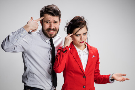 conflicting: The funny sad business man and woman conflicting on a gray background. Business concept  of relationship of colleagues. concept - youre crazy