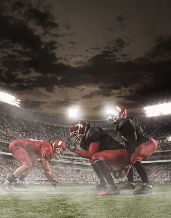 floodlit: The american football players in action in stadium Stock Photo