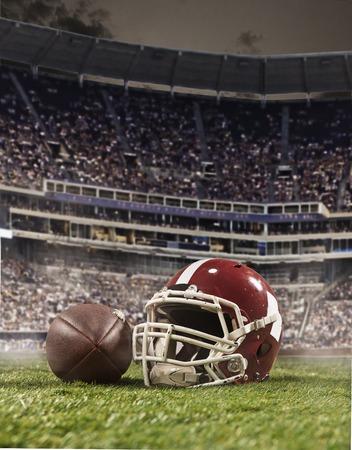 スタジアムの背景にヘルメットとアメリカン フットボール選手のボール