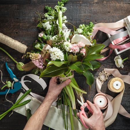 Las manos de floristería en contra de escritorio con herramientas de trabajo y las cintas sobre fondo de madera