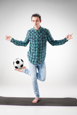 meditator: Portrait  of young man, practicing yoga with football ball on gray background. concept of continuous soccer practice
