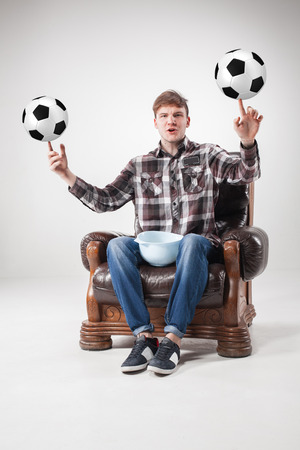 the admirer: A portrait of a fan with balls , sitting and holding a dish on gray background